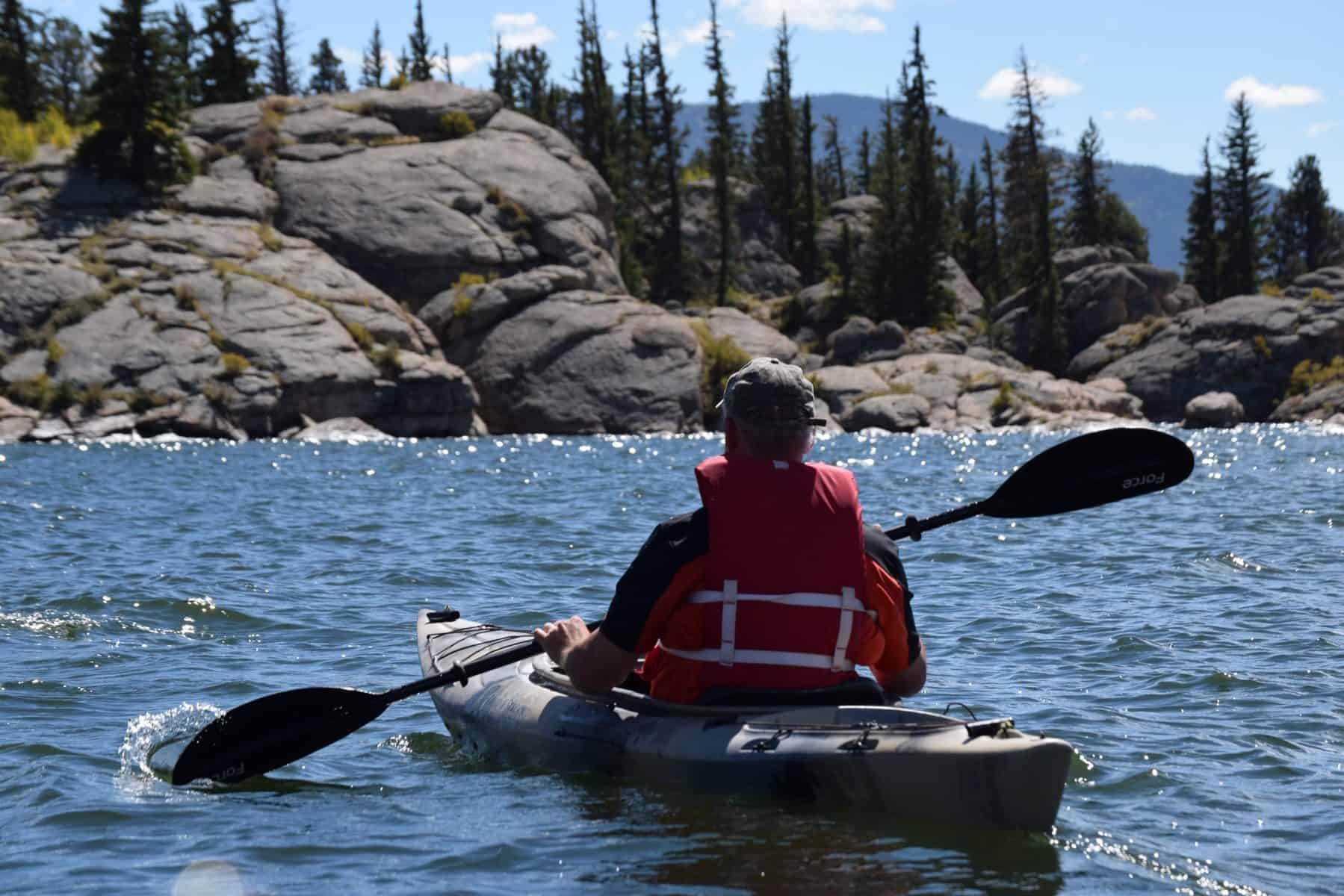 A Kayakers Paddling With A LIfe Vest On