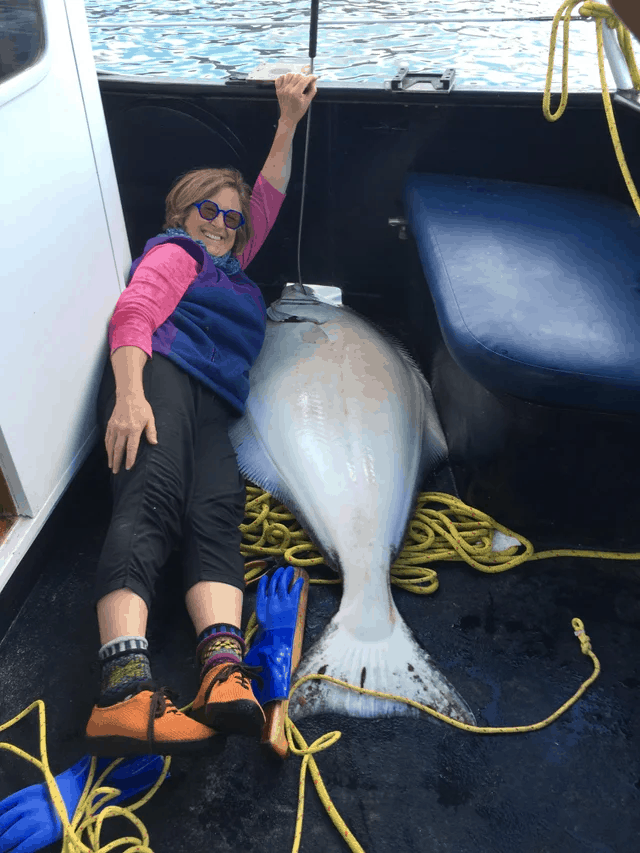 Woman lying next to Halibut catch