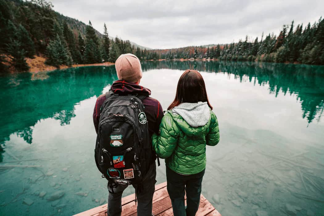Couple Near Lake Wearing Backpack